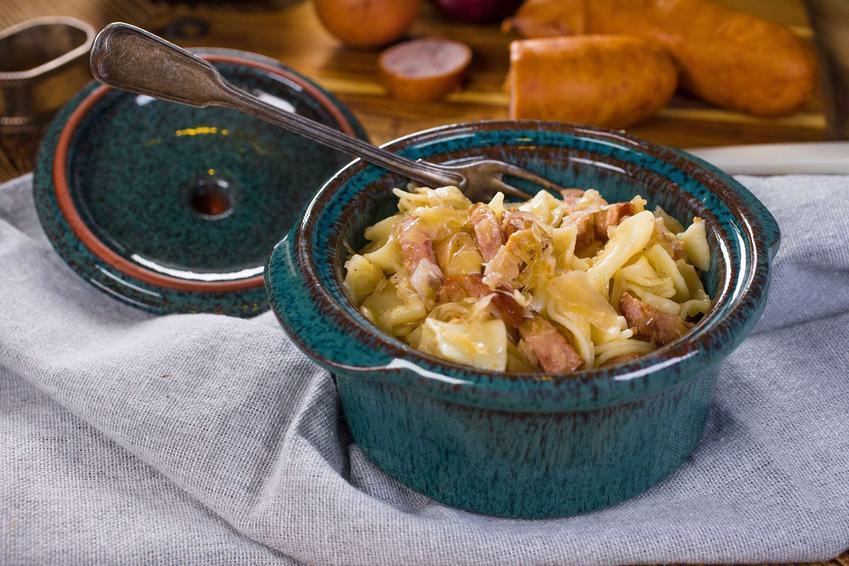 Niebieski garneczek z łazankami z mięsem, w które włożony jest z tyłu widelec.