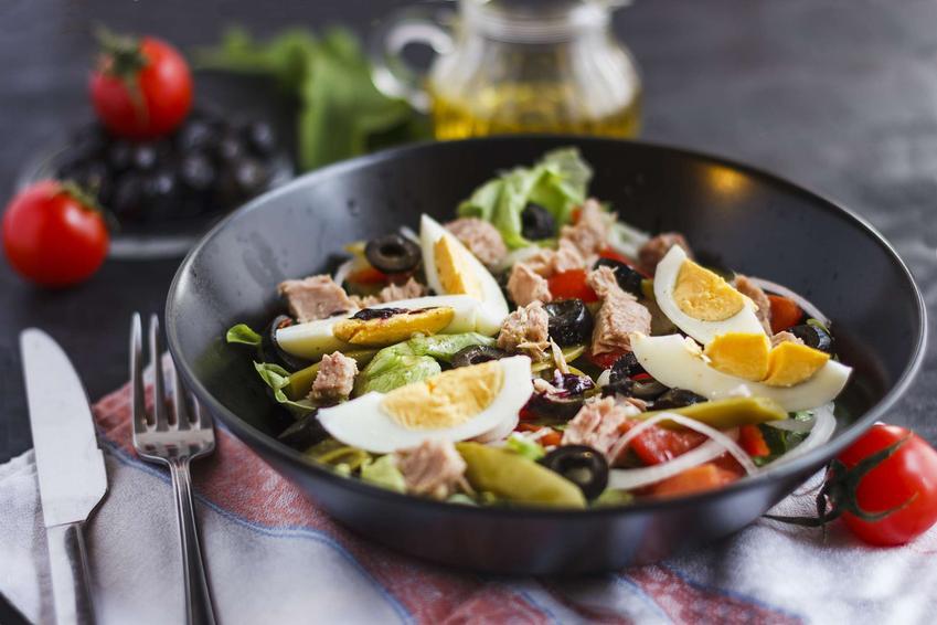 Sałatka z kolorowymi warzywami i tuńczykiem w eleganckiej misce. Z ćwiartkami ugotowanego jaja na wierzchu.