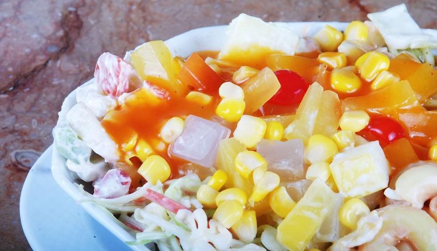 Sałatka z makaronem ryżowym z dodatkiem kukurydzy znajduje się w miseczce, która postawiona jest na blacie stołu.