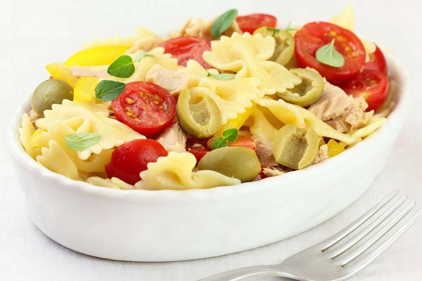 Sałatka z makaronem kokardki znajduje się w podłużnej misce. W sałatce dostrzegamy dodatek mięsa z kurczaka i pomidorków.