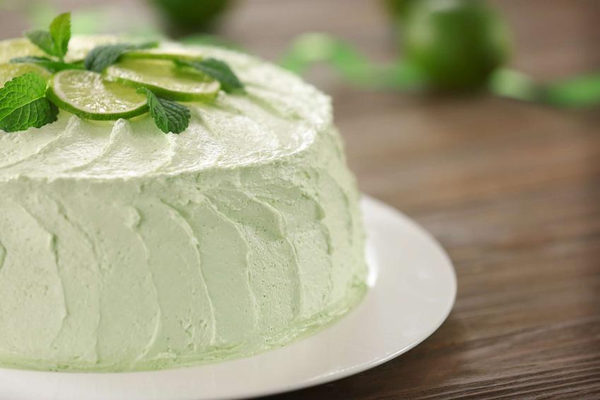 Tort mojito podany na eleganckim talerzu, udekorowany limonką i miętą.