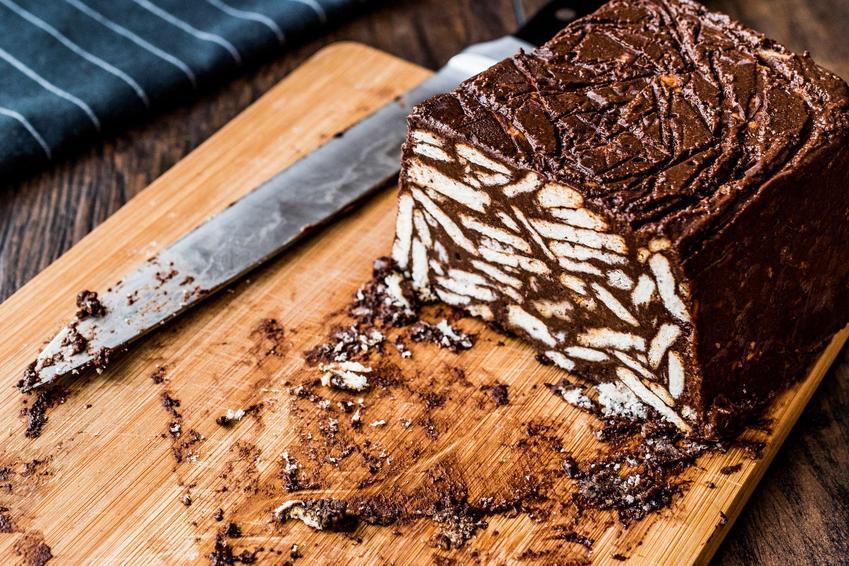Blok czekoladowy z herbatnikami znajduje się na desce do krojenia. Obok leży nóż.