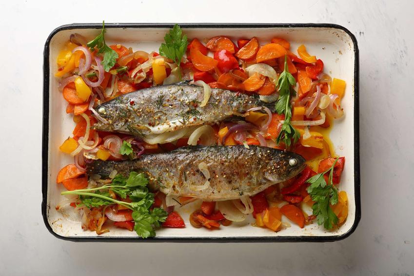 Pstrąg pieczony z warzywami ułożony w naczyniu żaroodpornym.