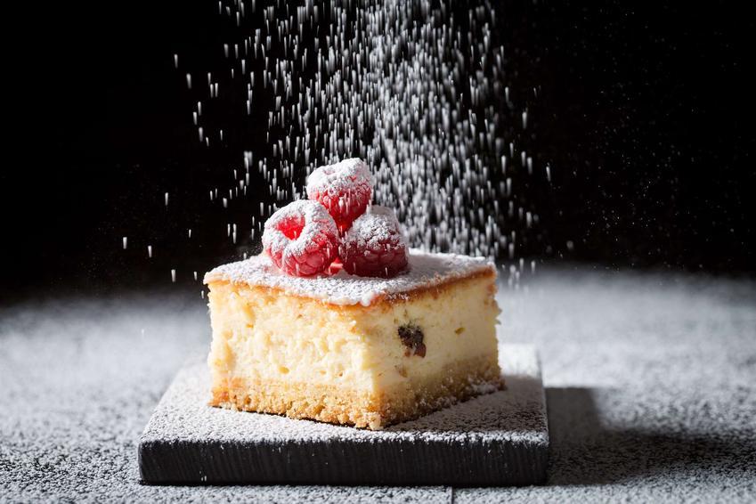 Sernik gotowany na biszkopcie obsypany cukrem pudrem i podany z malinami.