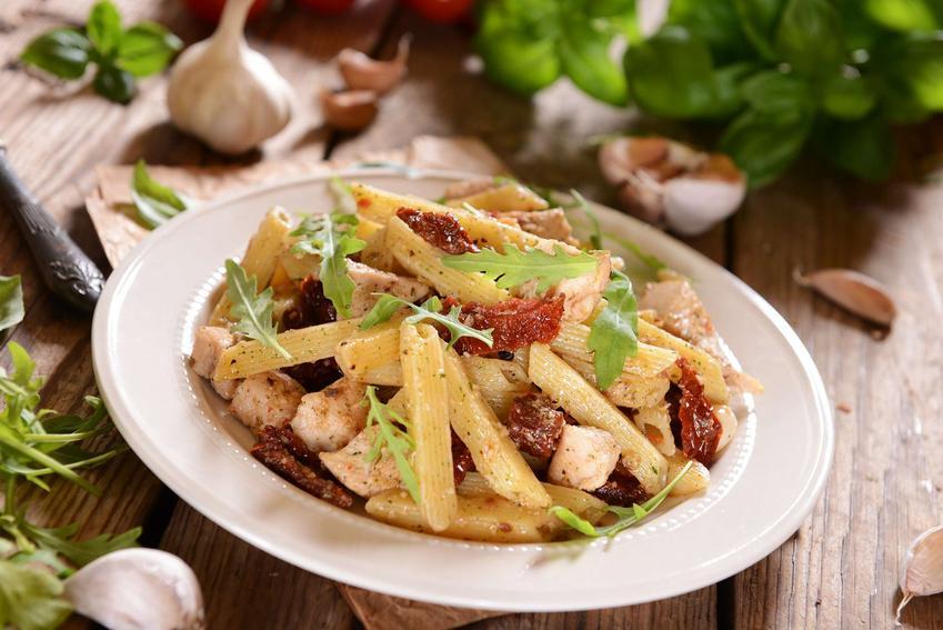 Sałatka z makaronem i suszonymi pomidorami znajduje się na białym talerzu, który znajduje się na blacie. na talerzu znajduje się makaron, suszone pomidory, mięso z piersi kurczaka oraz sos sałatkowy.