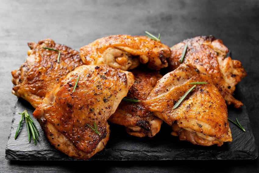 Upieczone udka z kurczaka znajdują się na czarnej deseczce.