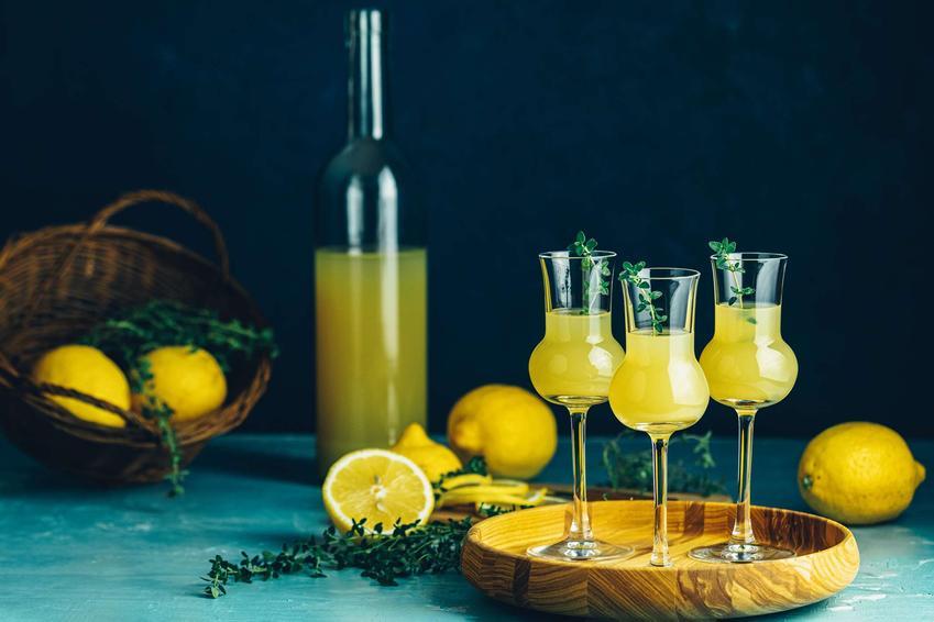 Limoncello podane w wysokich kieliszkach na drewnianej tacy, w tle butelka z limoncello, cytryny i kosz z cytrynami