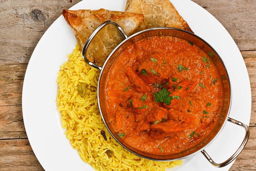 Czerwone curry podane z dodatkiem ryżu. Całość znajduje się na białym talerzu.