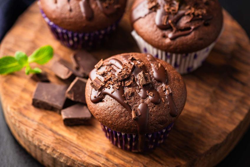 3 muffinki czekoladowe na okrągłej, drewnianej desce.