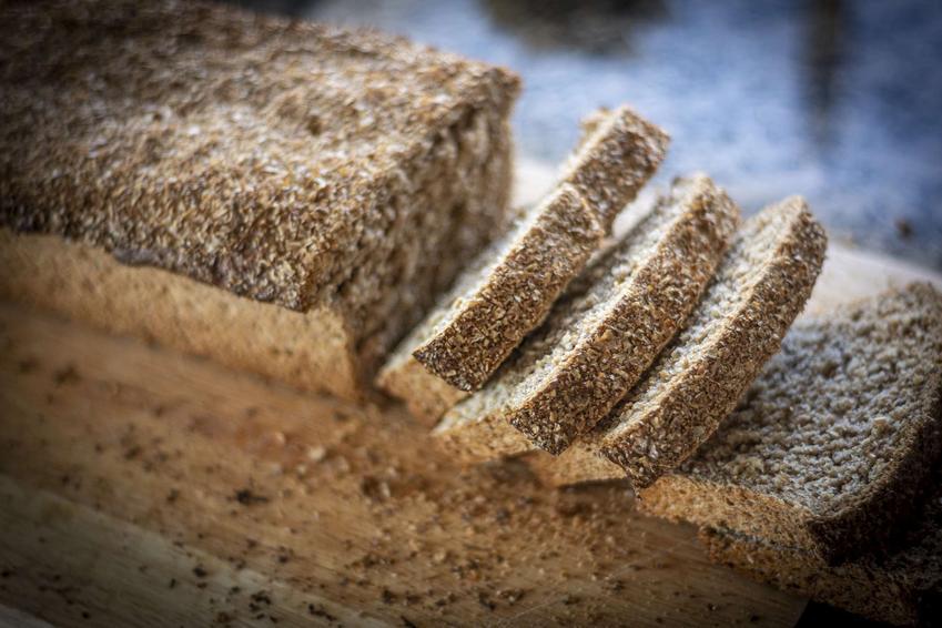 Chleb graham podany na drewnianej desce.