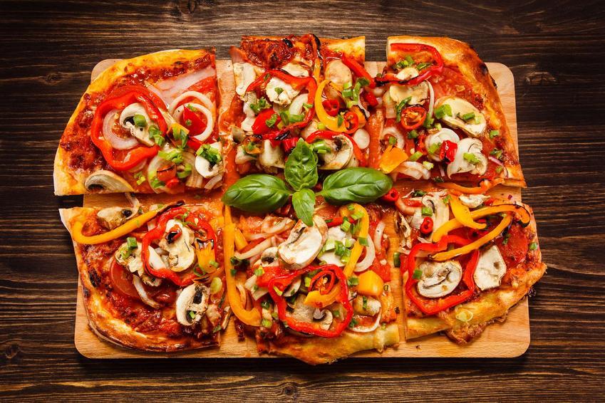 Upieczona vege pizza o prostokątnym kształcie znajduje się na drewnianym blacie.