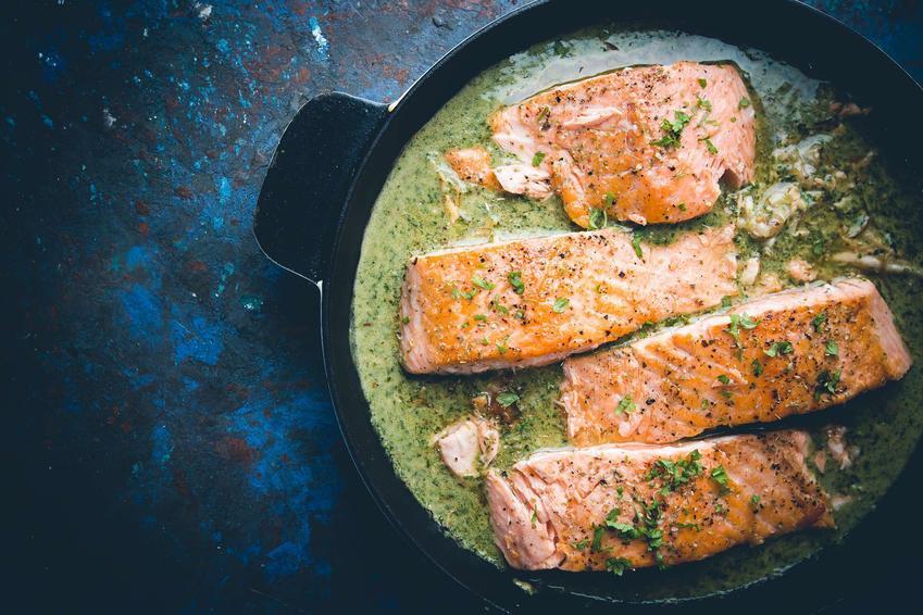 Ryba ze szpinakiem podana na patelni.