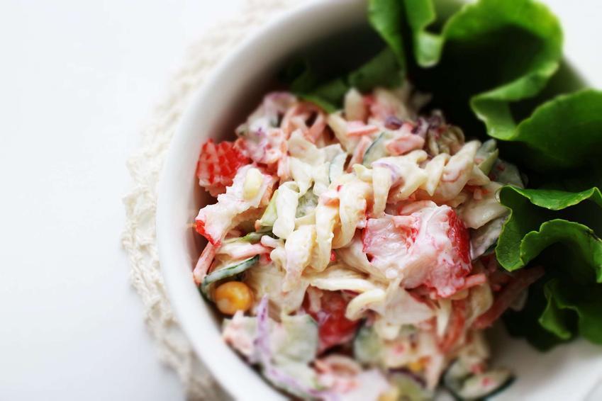 W białej miseczce na białym tle znajduje się sałatka z makaronem i majonezem. Całość przyozdobiona jest zielonym liściem sałaty. W sałatce dominuje makaron, papryka i majonez.
