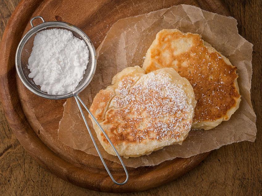 Racuchy wigilijne ułożone na papierze do pieczenia. Posypane są cukrem pudrem. Obok racuchów znajduje się sitko z cukrem pudrem.