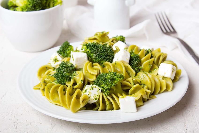 Sałatka z brokułem, fetą i makaronem ułożona jest na talerzu. Na drugim planie znajduje się miseczka z różyczkami brokuła oraz widelec. Wszystko to leży na białym blacie.
