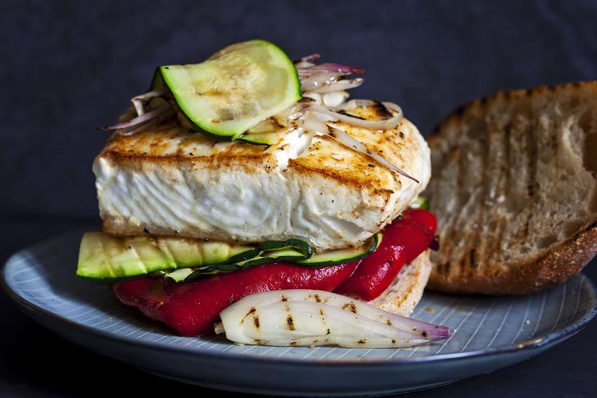 Ryba w papilotach podana jest na błękitnym talerzu. Udekorowana jest plastrem cukinii.