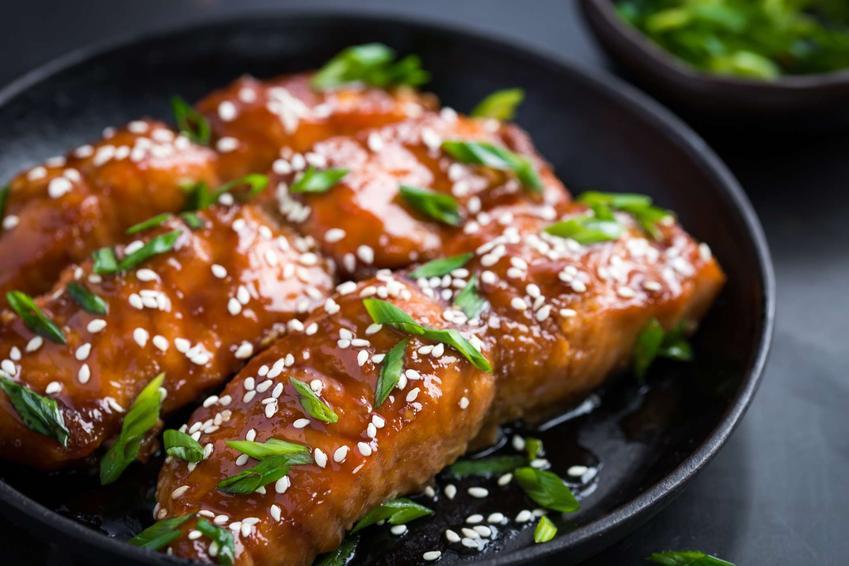 Ryba w sosie słodko-kwaśnym podana jest na czarnym, okrągłym talerzu.
