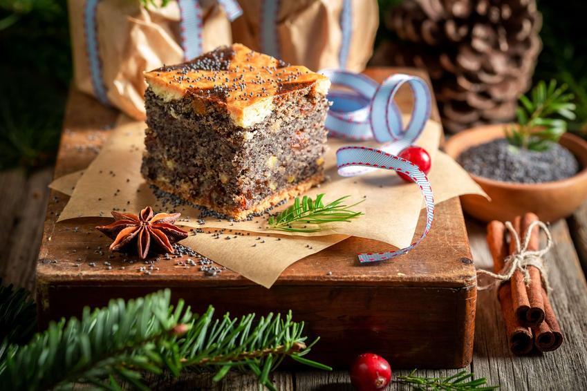 Makowiec na biszkopt ie podany na drewnianej desce. Dookoła niego znajdują się bożonarodzeniowe ozdoby.