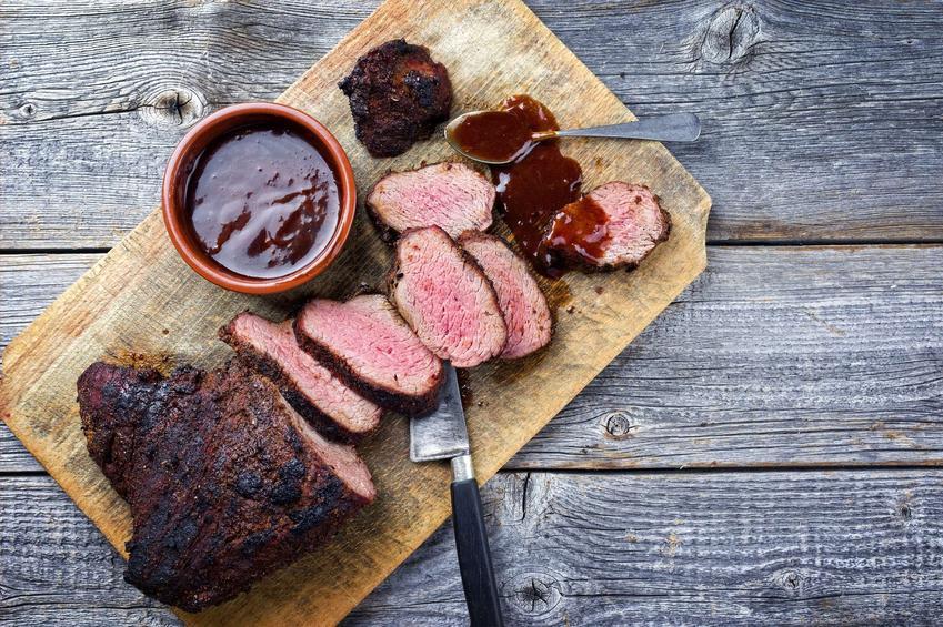 Sos pieczeniowy ciemny podany jest dodatkiem mięsa na drewnianej desce.