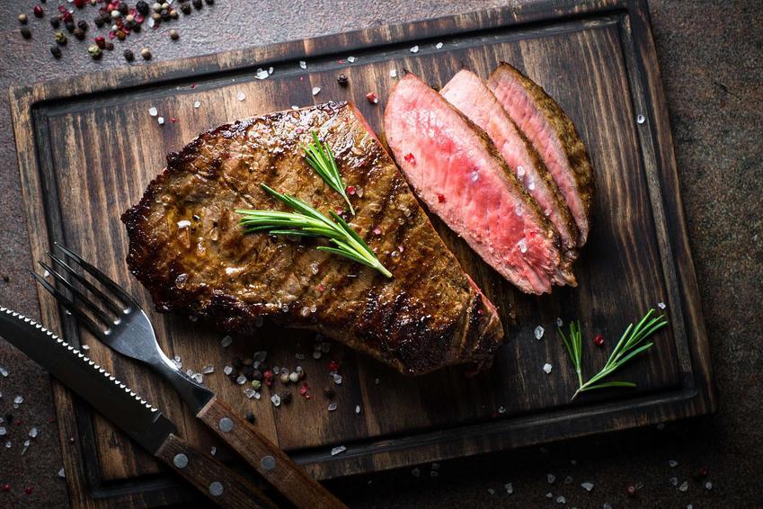 Stek z polędwicy wołowej podany jest na drewnianej desce. Na desce poza stekiem leży jeszcze nóż i widelec.