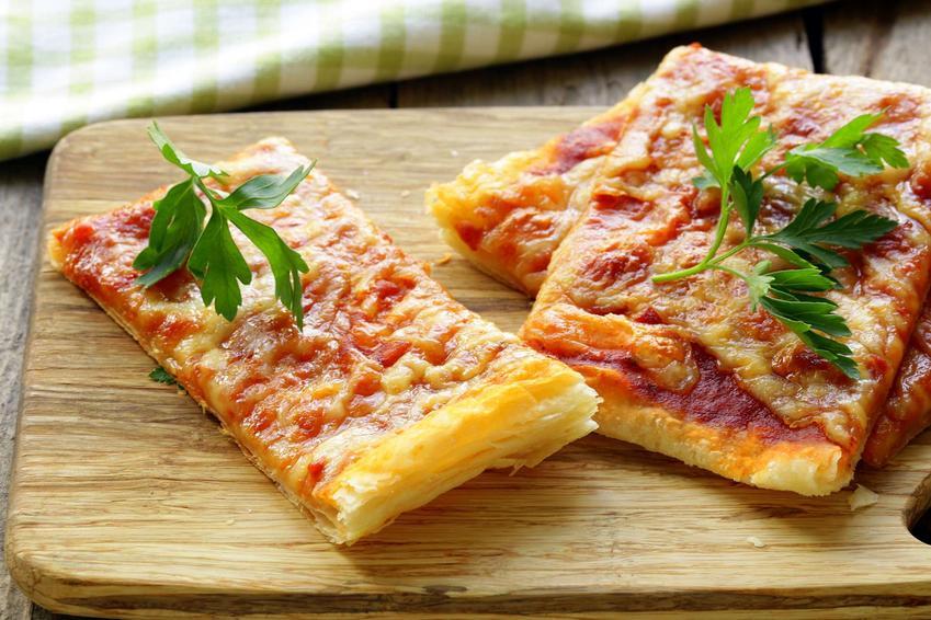 Pizza na cieście francuskim z serem mozzarella i sosem pomidorowym leży pokrojona na drewnianej desce do krojenia. Pizza jest udekorowana natką pietruszki.