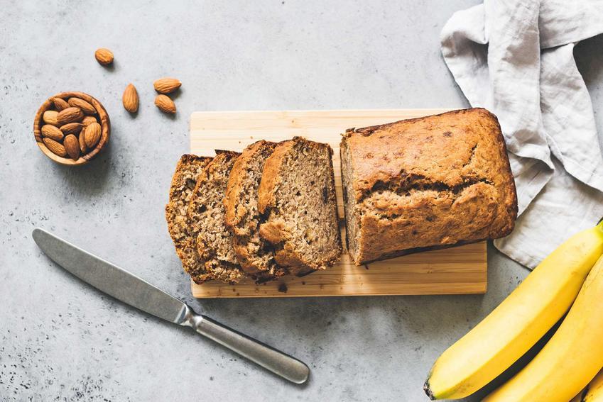 Ciasto z bananami pokrojone jest na kawałki i leży na desce. Obok deski znajduje się mały, metalowy nóż, banany oraz migdały.