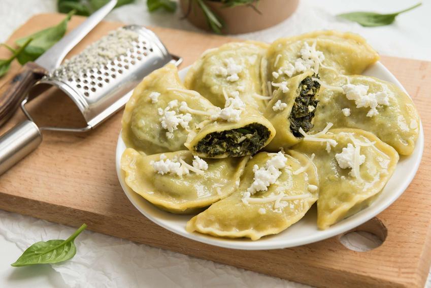 Pierogi ze szpinakiem i serem feta podane są na białym talerzu.