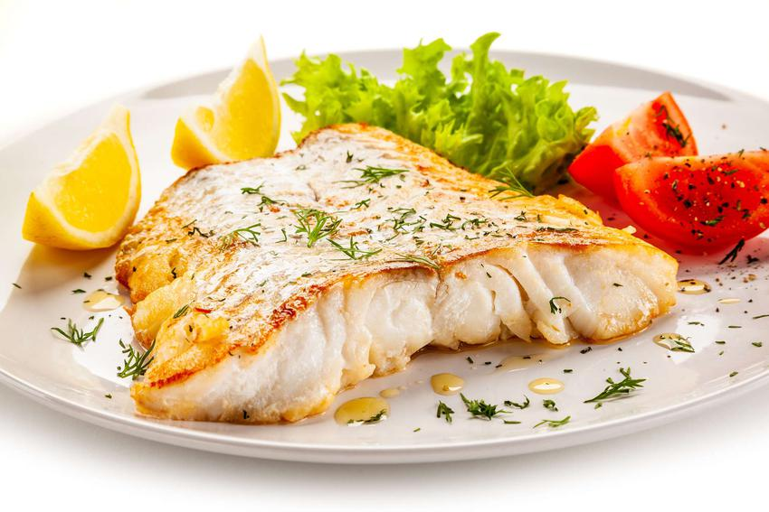 Polędwica z dorsza smażona podana jest na białym talerzu. Udekorowana jest kawałkami cytryny, liściem sałaty oraz ćwiartkami pomidora.