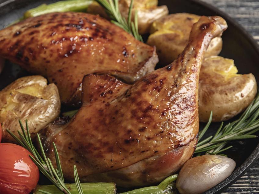Udka pieczone w rękawie podane są na talerzu z dodatkiem warzyw.
