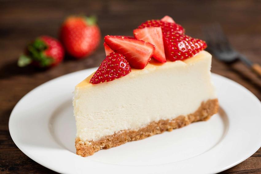 Sernik z wiaderka na herbatnikach podany jest na białym talerzyku. Kawałek ciasta udekorowany jest świeżymi truskawkami.