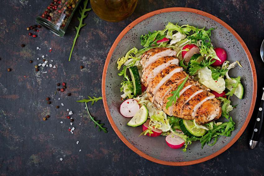 Pierś z kurczaka podana jest na okrągłym talerzu. Leży ona na bukiecie warzyw.