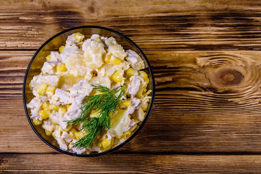 Sałatka z kurczakiem, ananasem i kukurydzą podana w  szklanej miseczce, stojącej na drewnianym blacie. Sałatka jest udekorowana natką pietruszki.