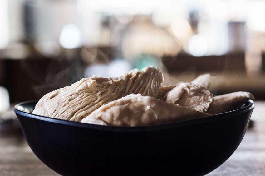 Gotowana pierś z kurczaka podana w czarnej miseczce.