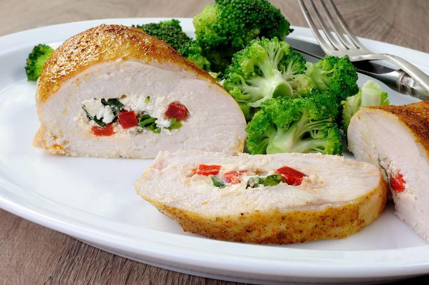 Pierś z kurczaka faszerowana podana z dodatkiem brokułów na białym talerzu.