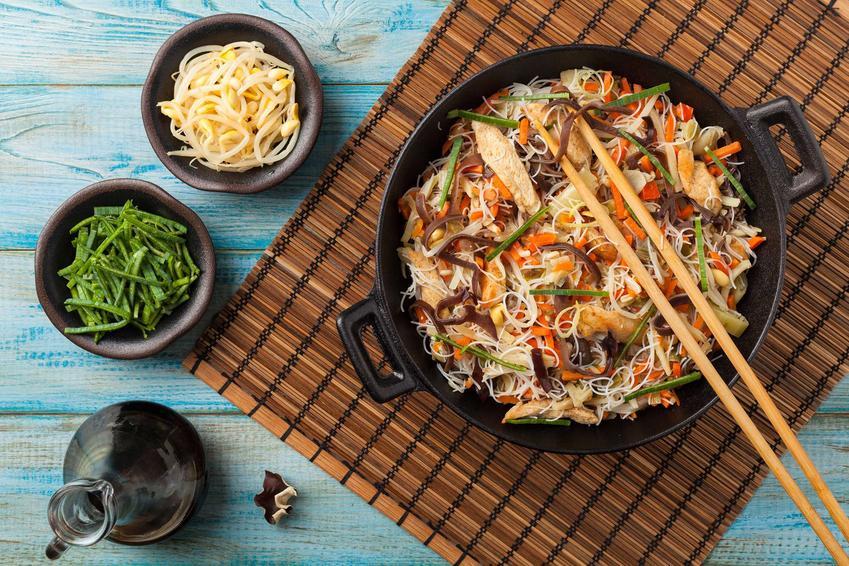 Makaron ryżowy z kurczakiem podany w żeliwnym garnku z warzywami.