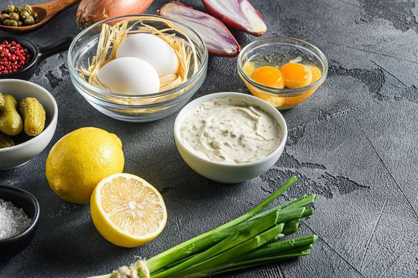 Jajka w sosie tatarskim są dopiero przygotowywane. Składniki do ich przygotowania leżą na blacie.