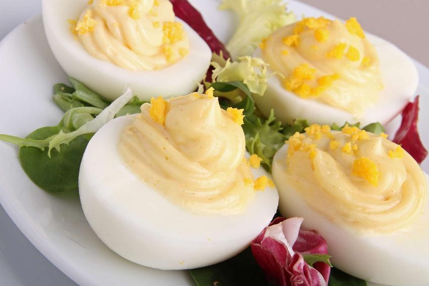 Jajka w majonezie leżą na białym talerzu.