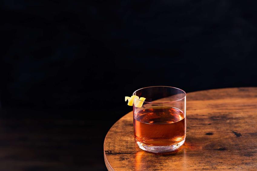 Sazerac podane jest w szklance, która stoi na drewnianym stole.