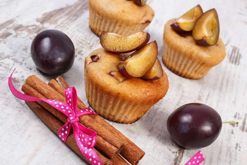 Muffiny ze śliwkami podane są na marmurowym blacie. Ozdobione są świeżymi śliwkami.