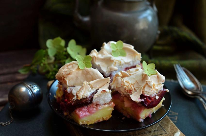 Tartę z bezą i śliwkami podana na małym, ciemnym talerzyku.