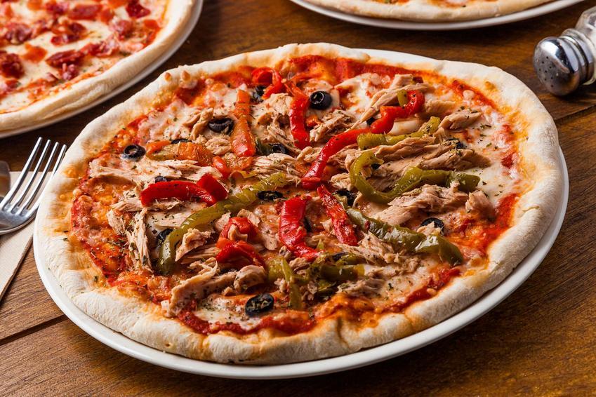 Pizza z tuńczykiem podana na eleganckim talerzu z warzywami.