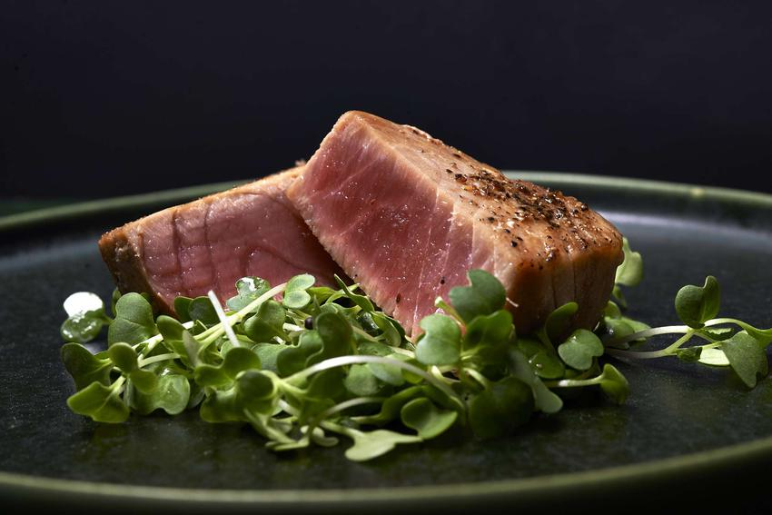 Polędwica z tuńczyka podana na eleganckim talerzu z sałatą.