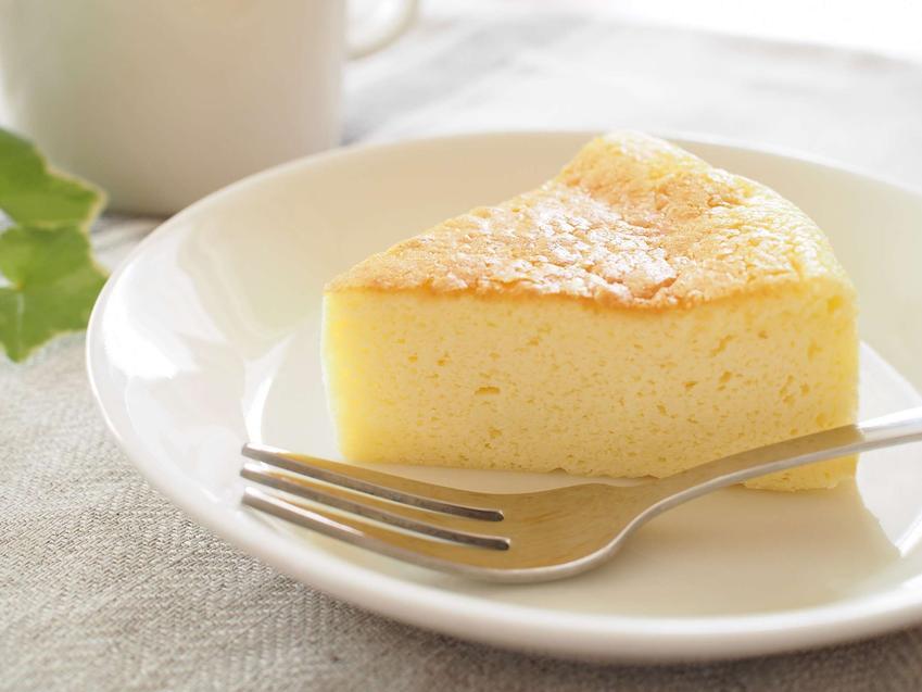 Kawałek sernika gotowanego z wiaderka na białym talerzyku. Obok ciasta leży widelczyk do ciasta.