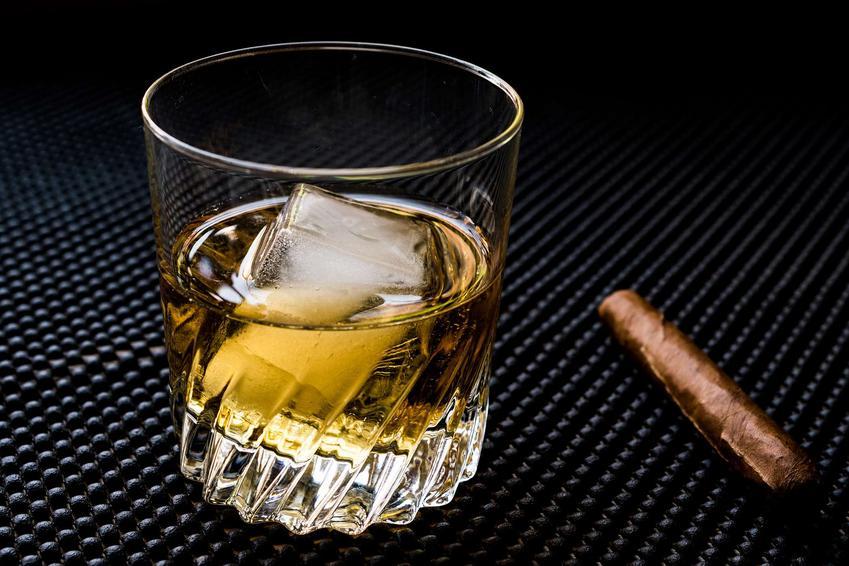 Godfather drink podany w szklance. Obok szklanki leży cygaro.