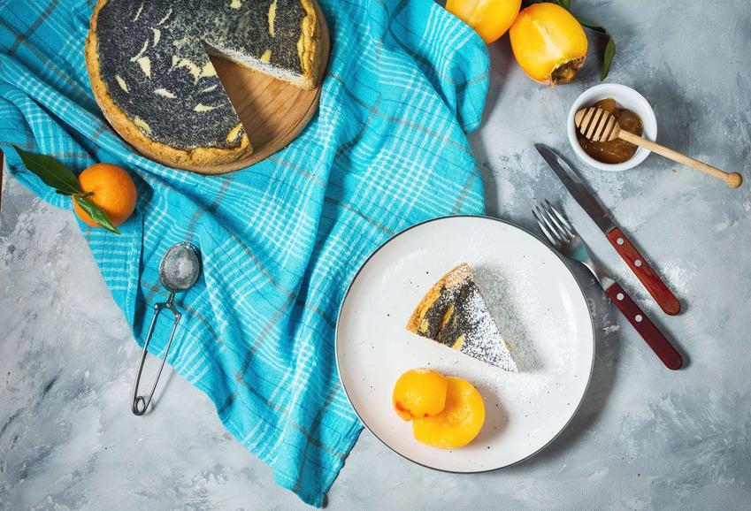 Biały, okrągły talerzyk z seromakowcem z brzoskwiniami. Obok leżą sztućce, niebieska ściereczka, na której stoi reszta ciasta, miód i świeże owoce.