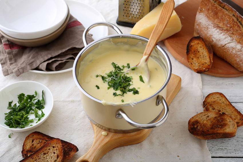 Zupa serowa podana w dużym garnku z grzankami.
