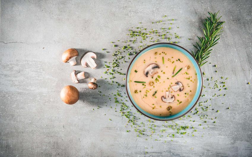 Zupa pieczarkowa z serkiem topionym podana w miseczce i udekorowana ziołami.