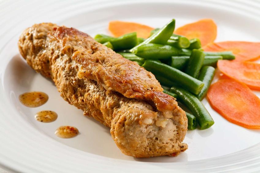 Roladka schabowa z piekarnika z zieloną fasolką szparagową oraz plasterkami marchewki na białym talerzu.