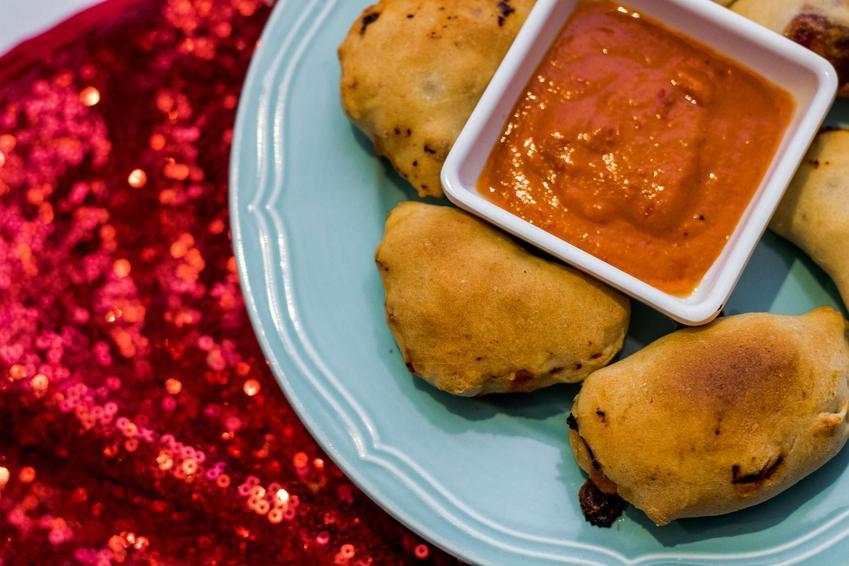 Pierogi włoskie z sosem pomidorowym na błękitnym talerzu. W tle znajduje się czerwony, cekinowy materiał.