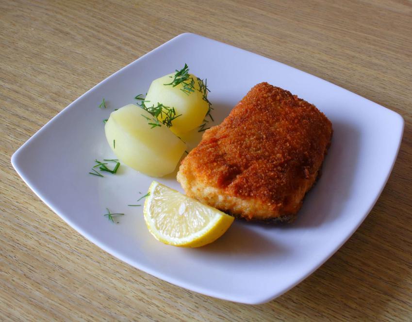 Kawałek seleryby, na białym talerzyku, z ugotowanymi ziemniakami i kawałkiem cytryny